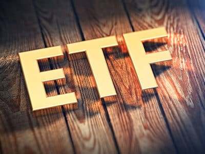 """The acronym """"ETF"""" is lined with gold letters on wooden planks."""