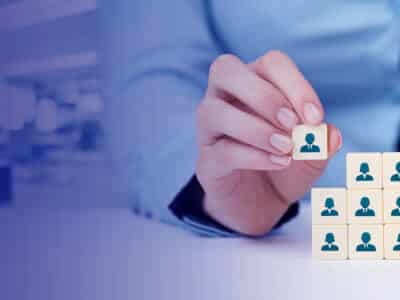 Human resources as a concept. Businesswoman complete team by one person (employee) represented by icon. Wide banner composition with office in background.