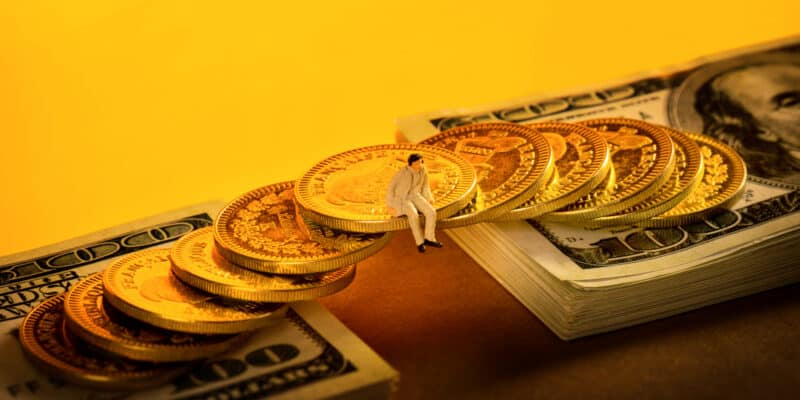 A closeup of a small person figure sitting on a coin bridge on dollar bills - concept of investment