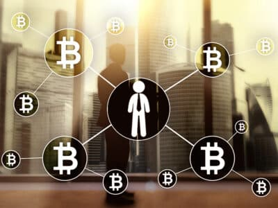 Bitcoin cryptocurrency on blurred skyscrapers background.
