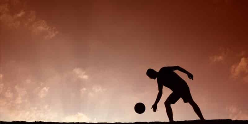 Silhouette of man playing with ball