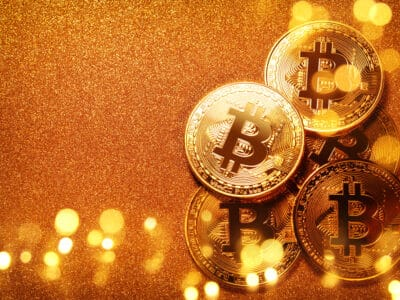 Bitcoin over gold glitter background. Business concept